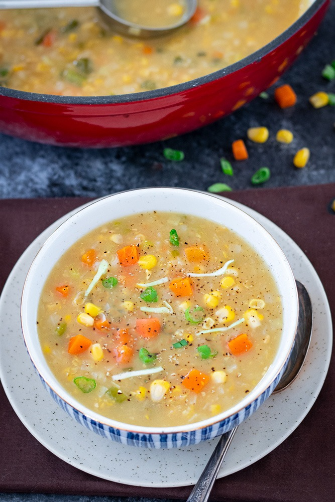 Corn soup topped with carrots, scallions