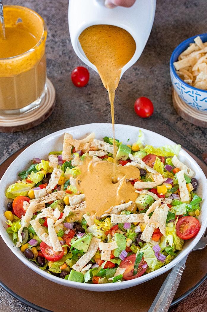 Pour chipotle dressing on salad
