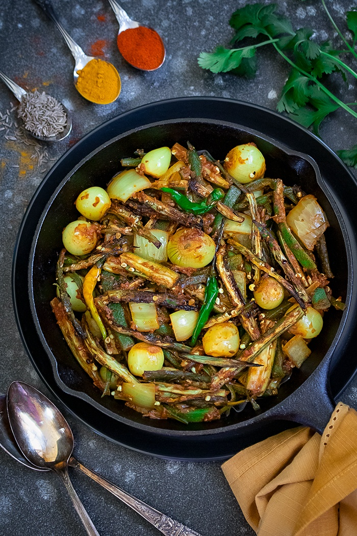 Bhindi do pyaza in a black pan with spices on the side