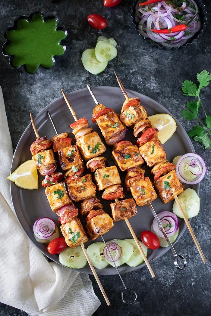 Achari Paneer Tikka on skewers with chutney and onions