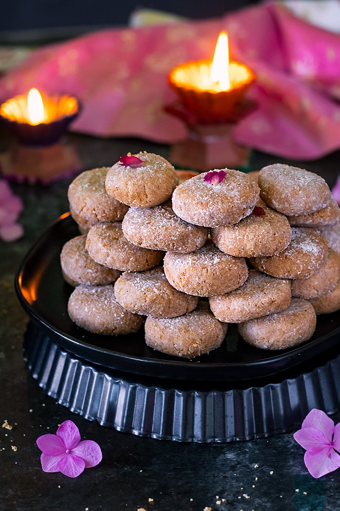 Mathura ke Pede stacked in a plate with candle lit in the background