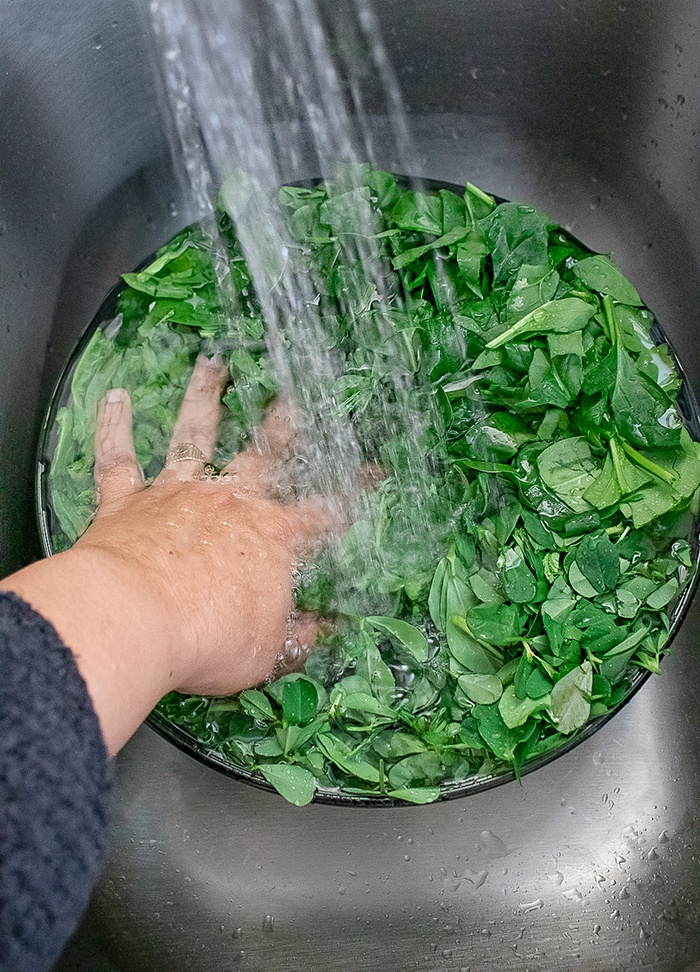 Wash the winter greens under tap water