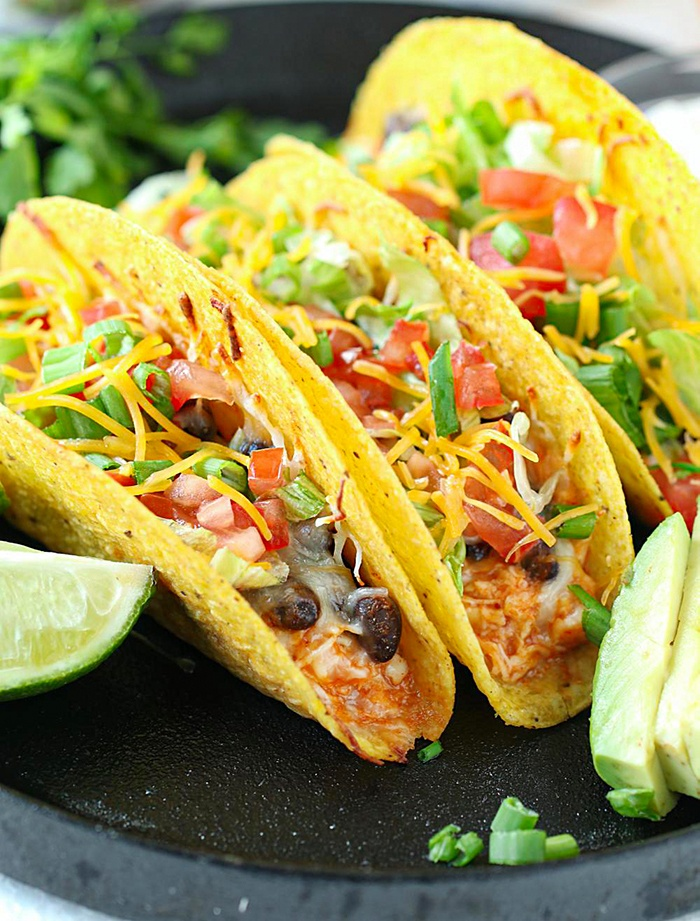 Chicken and bean tacos on a tray with avocados