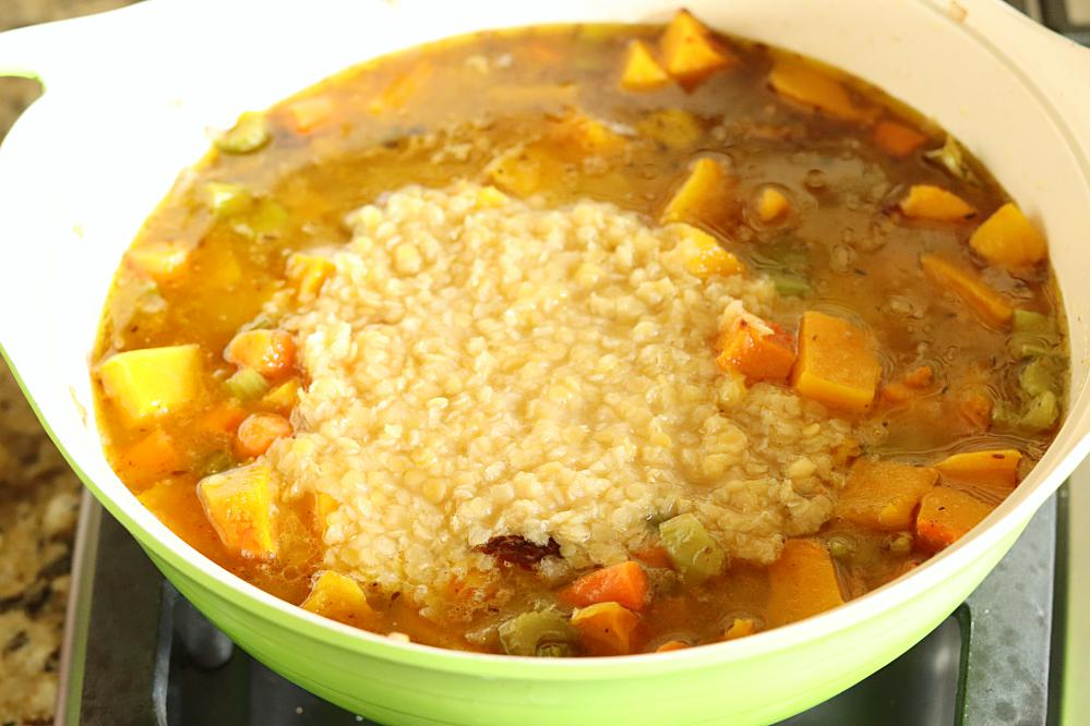 Butternut squash and lentil soup cooking in a pan