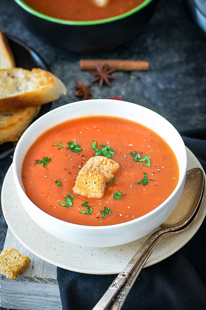 Tamatar ka shorba - Spiced Indian Tomato soup with spoon and bread in a white bowl