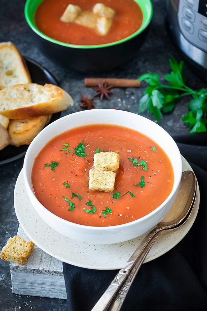 Tamatar ka shorba - Spiced Indian Tomato soup with bread and cilantro in the back
