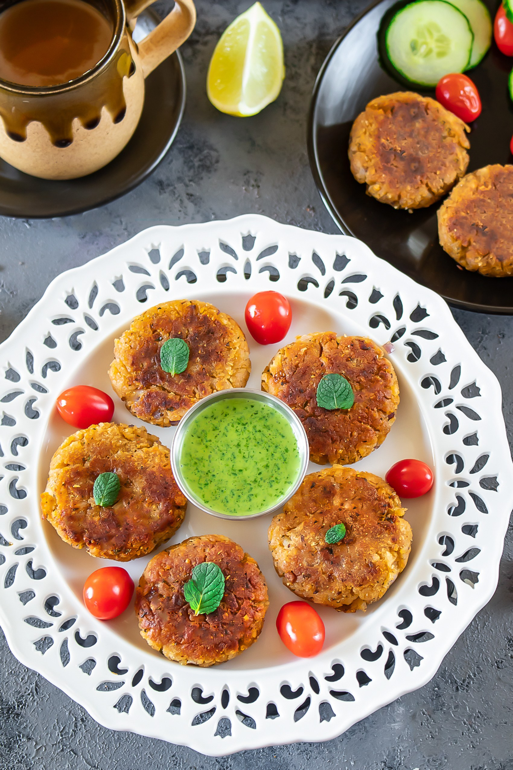 Oats and poha cutlets in a plate withtomatoes