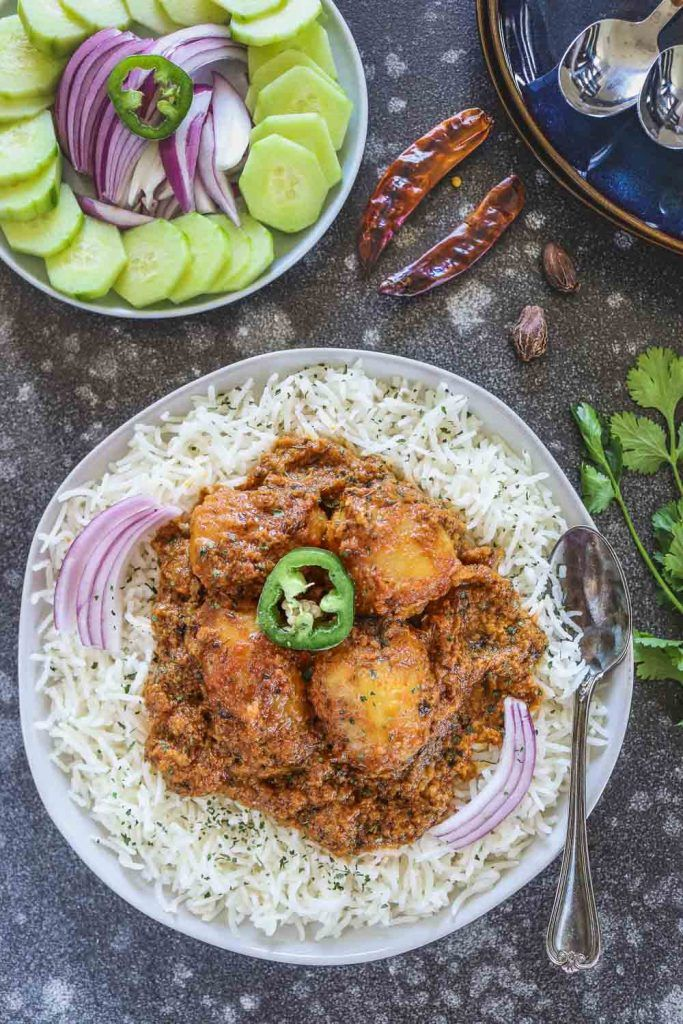 Instant Pot Dum Aloo over rice in a plate - Ruchiskitchen
