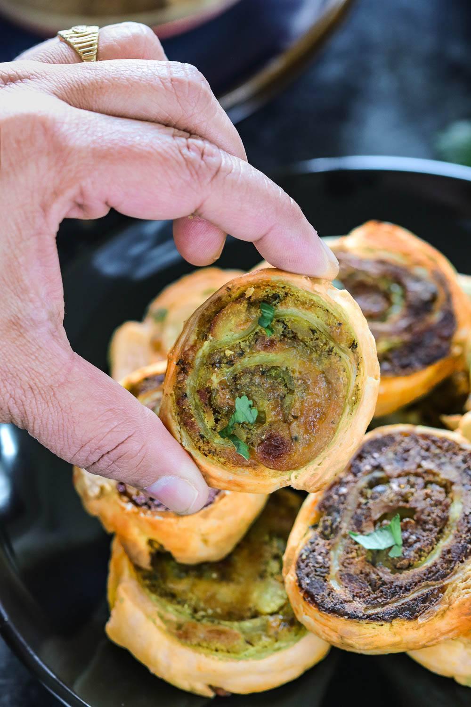 Puff Pastry Samosa Pinwheels in hands - Ruchiskitchen