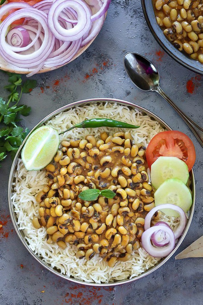 Instant Pot Black Eyed Peas Curry in a plate with rice and salad on side- Ruchiskitchen