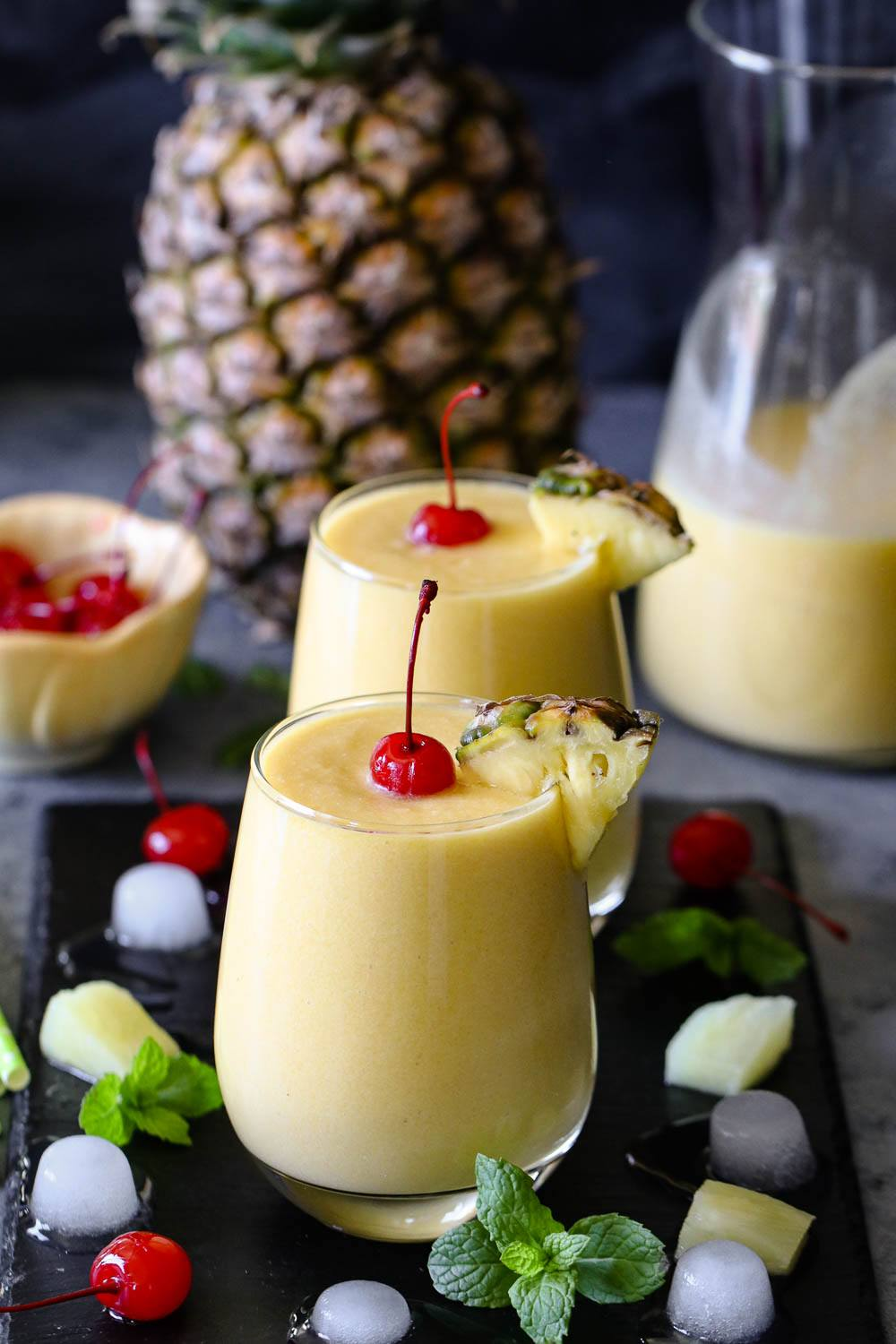 Pineapple Mango Piña Colada  with pineapple and cherries in the background.