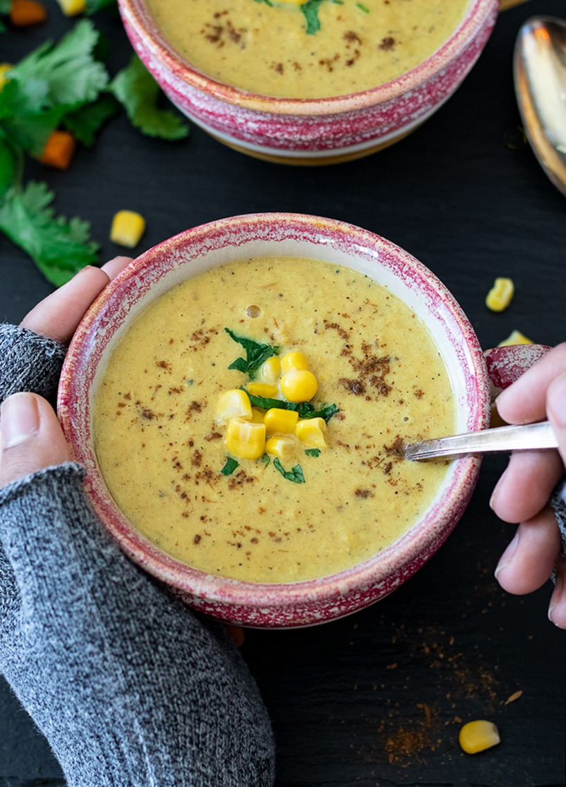 Hands holding the Makai Ka Shorba (Spiced Corn Soup)