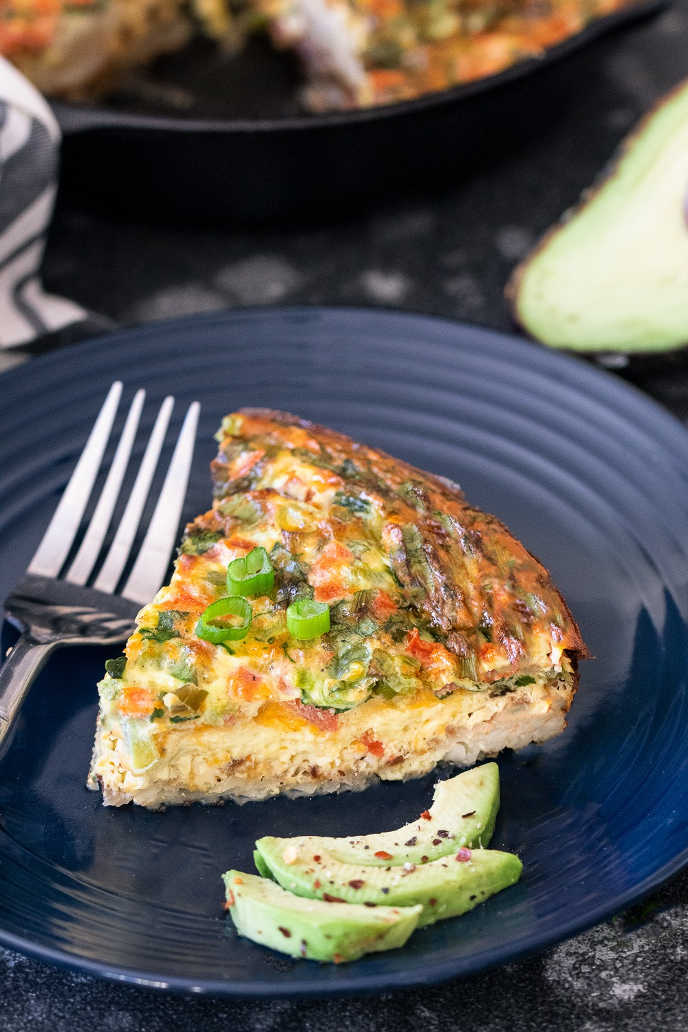 Hash Brown Frittata wedge on a blue plate with fork and avocado slices