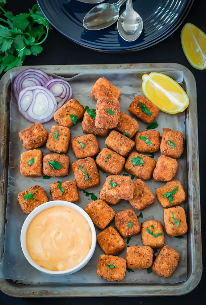 Spicy paneer bites on a tray with onion and lemon wedge