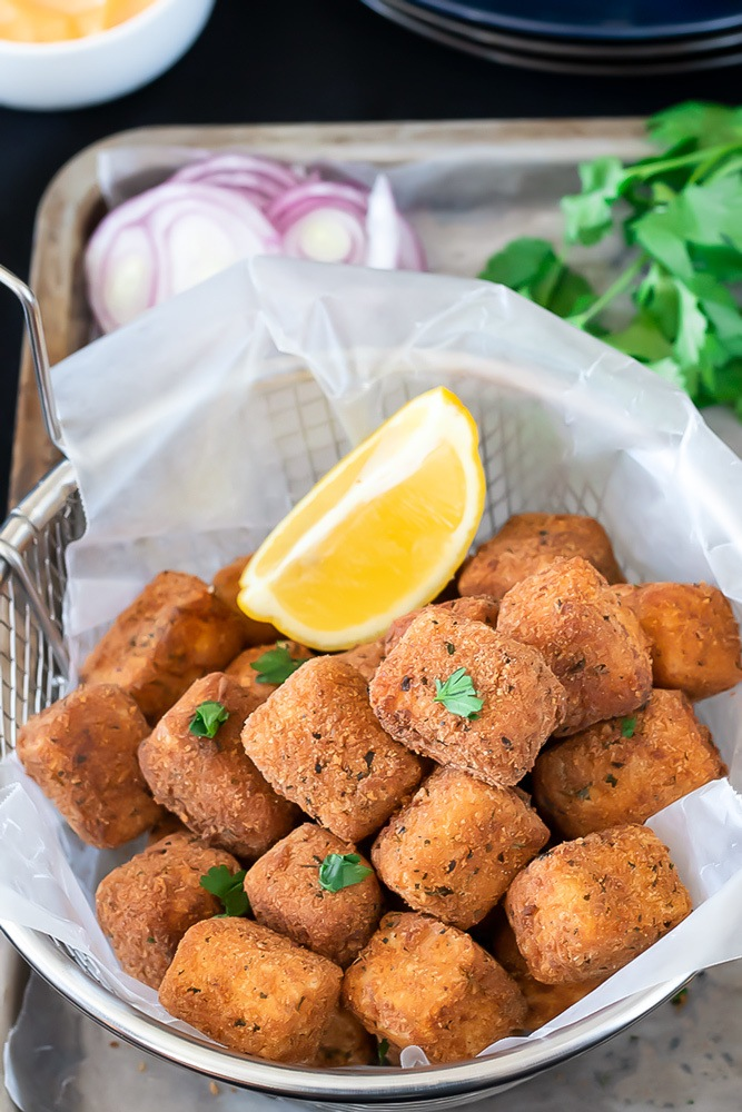 Spicy paneer bites with a lemon wedge in a basket