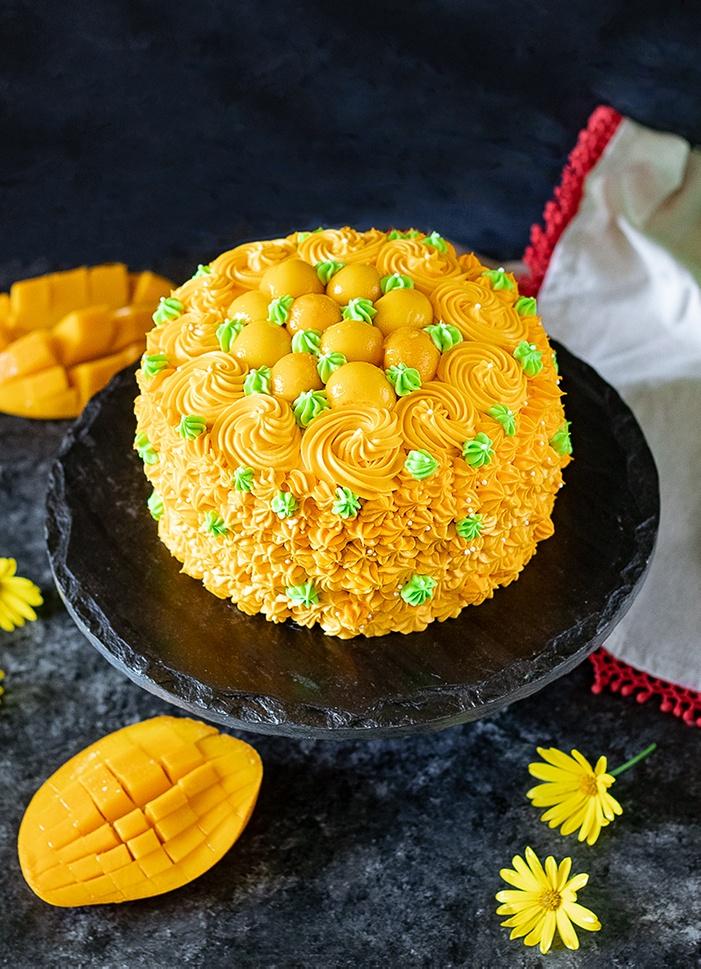 Eggless mango cake with frosting and fresh mangoes