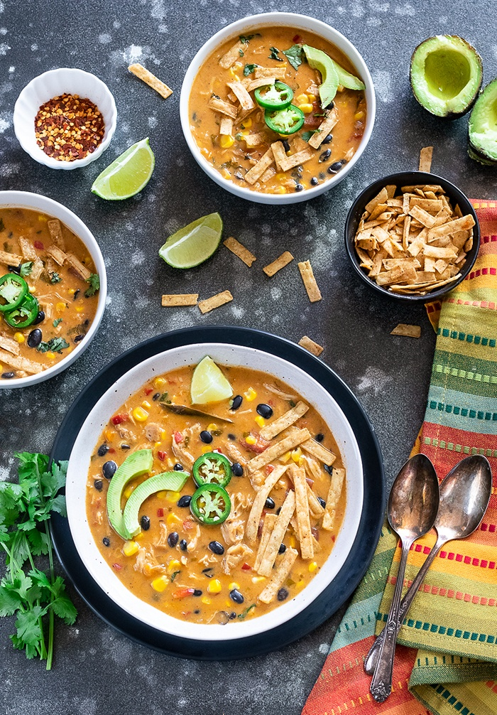 Instant Pot Creamy Chicken Tortilla Soup garnished with avocados and tortilla strips